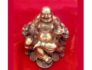 brass laughing buddha sitting on a dragon chair
