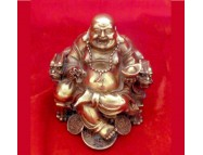 brass laughing buddha sitting in a dragon chair